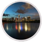 Clouds Roll Over The Austin Skyline As The Neon Reflects In The Glass-like Waters Of Lady Bird Lake Round Beach Towel