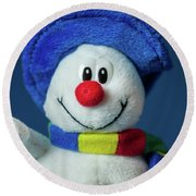 A Cute Little Soft Snowman With A Blue Hat And A Colorful Scarf Round Beach Towel