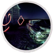 A Light Painted Scene Of A Rusty Caddy By A Barn And Cornfield Round Beach Towel