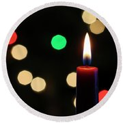 A Red Christmas Candle With Blurred Lights Round Beach Towel