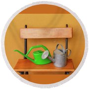 A Watering Can Of  Aluminium And A Plastic One Laid On Wooden Bench Round Beach Towel