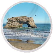 Arch In The Sea With Pelicans Flying By, At Natural Bridges State Beach, Santa Cruz, California Round Beach Towel