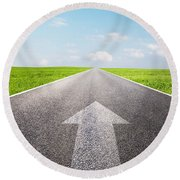 Arrow Sign Pointing Forward On Long Empty Straight Road Round Beach Towel
