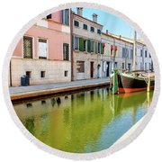 boat in a canal of the colorful italian village of Comacchio in  Round Beach Towel