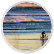 Cyclist Pedals Against The Wind At Pismo Beach Round Beach Towel