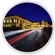 Indigo Sky And Car Lights Over Plaza Espana And Puente Nuevo Bri Round Beach Towel