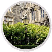 Lamppost In Front Of Green Bushes And Old Walls. Round Beach Towel