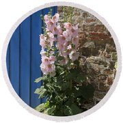 Pink Hollyhocks Growing From A Crack In The Pavement Round Beach Towel