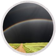 Rainbow And Darkened Skies Seen Down A Country Road Round Beach Towel