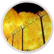 Realistic Orange Fire Explosion Behind Restricted Area Barbed Wire Fence, Blurred Background Round Beach Towel