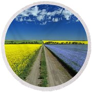 Road Through Flowering Flax And Canola Round Beach Towel