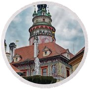The Cesky Krumlov Castle Tower With A Fountain Below Within The Czech Republic Round Beach Towel