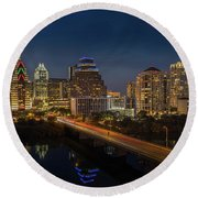 The Glimmering Neon Lights Of The Downtown Austin Skyscrapers Illuminate The Skyline Over Lady Bird Lake Round Beach Towel