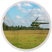 The Helicopter Over A Green Airfield. Round Beach Towel
