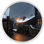 The Village Of Heptonstall In The Snow At Night With Lamps Shini Round Beach Towel