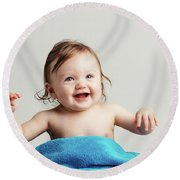 Toddler With A Cozy Blanket Sitting And Smiling. Round Beach Towel