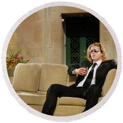 Wealthy Young Man In Suit Sitting On A Couch With A Drink On A T Round Beach Towel