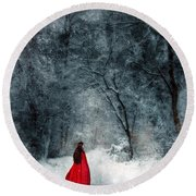 Woman In Red Cape Walking In Snowy Woods Round Beach Towel