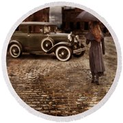 Woman With Umbrella By Vintage Car Round Beach Towel