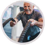 Senior Man Exercising With Ropes At The Gym. Round Beach Towel