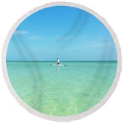 A Man Rides A Paddleboard In The Shallow Waters Near The City Pi Round Beach Towel