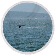 A Whale's Tail Above Water With Sail Boat In The Background Round Beach Towel