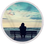 Man In Hood Sitting On A Lonely Bench On The Beach Round Beach Towel