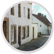 medieval cobbled street in Culross, fife Round Beach Towel