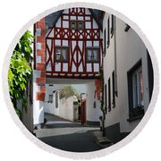 old historic street and woodframed house in Ediger Germany Round Beach Towel