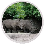 Pair Of Rhinos Standing In The Shade Of Trees Round Beach Towel