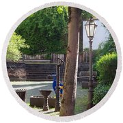 tree lamp and old water pump in Cochem Germany Round Beach Towel