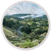 View Of Curved Road Through Dense Forest Area With Low Clouds Ov Round Beach Towel