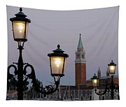 Lampposts Lit Up At Dusk With Building Tapestry