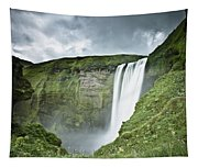 A Waterfall Over A Grassy Cliff Tapestry