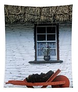 Wheelbarrow In Front Of A Window Of A Tapestry