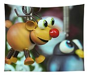 A Rudolph The Red Nosed Reindeer Ornament With A Penguin Tapestry
