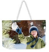 A Boy Throws A Snowball While Playing Weekender Tote Bag