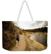 A Woman Jogging On A Dirt Trail Weekender Tote Bag