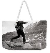 A Man Jumps From One Rock To Another Weekender Tote Bag