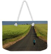A Woman Running On A Dirt Road Weekender Tote Bag