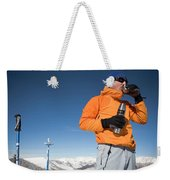 Dressed In Orange, A Skier Sips A Warm Weekender Tote Bag