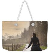 Victorian Woman Walking On A Cobbled Avenue At Sunset Weekender Tote Bag