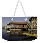Yellow Shikara In Front Of A Run Down Area Of Houses In The Dal Lake Weekender Tote Bag