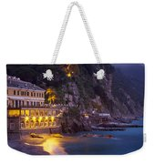 A Building Illuminated At Night Along Weekender Tote Bag