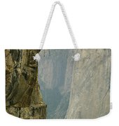 A Climber Makes His Way Up A Rock Face Weekender Tote Bag