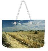 A Hay Field With Bales Sitting Weekender Tote Bag