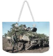 A Soldier Stands Beside A Camouflaged Weekender Tote Bag