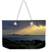 storm light - A morning light iluminates lighthouse through clouds in an amazing landscape Weekender Tote Bag
