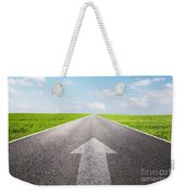 Arrow Sign Pointing Forward On Long Empty Straight Road Weekender Tote Bag