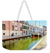 boat in a canal of the colorful italian village of Comacchio in  Weekender Tote Bag